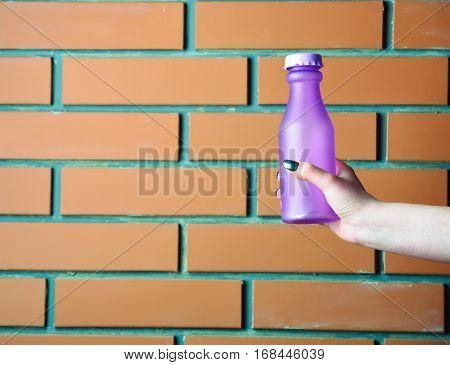 Violet Glass Or Plastic Bottle In Hand On Beige Background