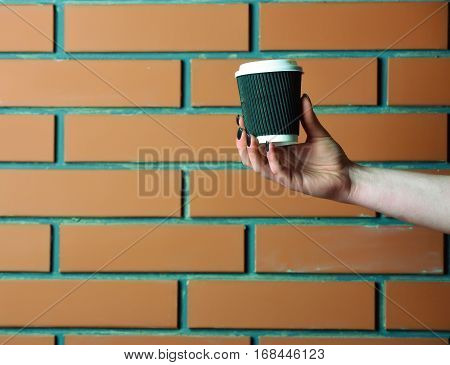 Paper Or Plastic Coffee Cup In Hand On Brick Wall