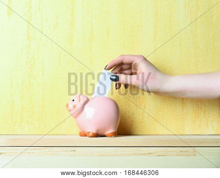 pink piggy bank or moneybox with paper in female hand as savings symbol on wooden board on yellow textured wall background copy space
