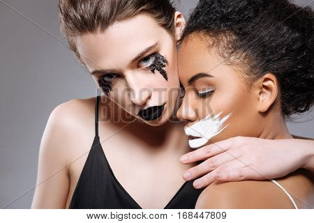 Attractive darkness. Two stunning elegant professional models representing opposite human qualities while acting on set and wearing contrasting looks
