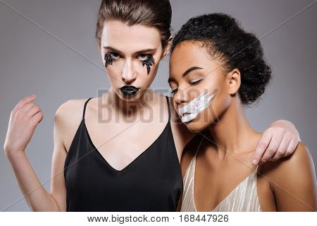 Necessity of contrasts. Graceful magnifying artistic women demonstrating conceptual looks of bad and evil while wearing creative makeup and contrasting dresses