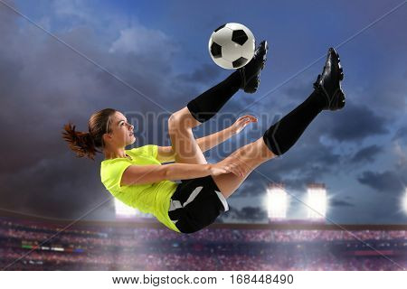 Female soccer player performing bicycle kick with large stadium in background