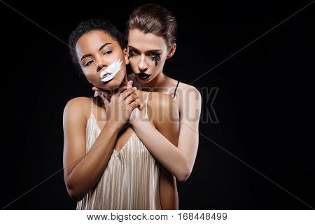 Darkness is taking over. Classy gorgeous young women showing opposition of light and darkness while posing for a photographer on set of a creative art project