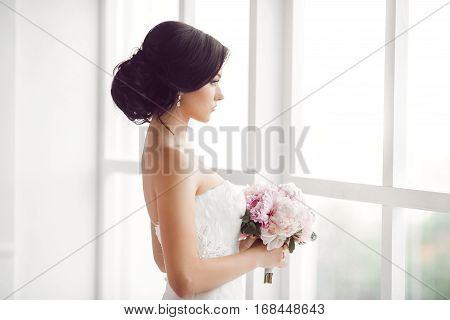 Beautiful bride. Wedding hairstyle make-up luxury fashion dress and bouquet of flowers. Young attractive multi-racial Asian Caucasian model like a bride against white room with big window looking away. Side view