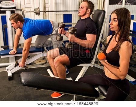 Friends in gym workout with fitness equipment. Fitness training women and men follow instructions of the coach. Group people working strong muscular on simulator his body at gym.