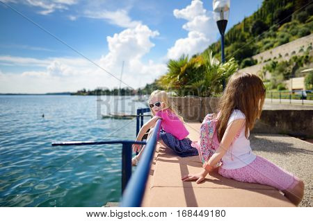 Two Cute Little Sisters Having Fun On A Shore Of Lake Garda In Toscolano-maderno, A Small Town And C