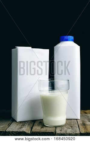 Glass with fresh organic milk and white drinking straw inside near plastic bottle with blue cap on pastel blue table. Space for you text above. Retail set rich texture