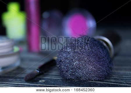 Makeup brush and cosmetics - concealer, blush, lipstick on wooden table and black background behind, beautiful bokeh.