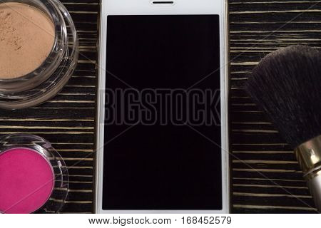 Smartphone with empty screen and cosmetics - concealer, blush, brush on wooden background for make up.