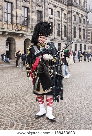 AmsterdamNetherlands-December 302016:Bagpiper with his bagpipe in the square. Nearby are walking tourists