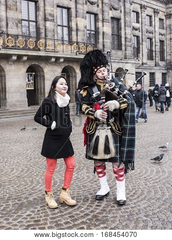 AmsterdamNetherlands-December 302016:Bagpiper with his bagpipe in the square. Woman photographed with him. Nearby are walking tourists