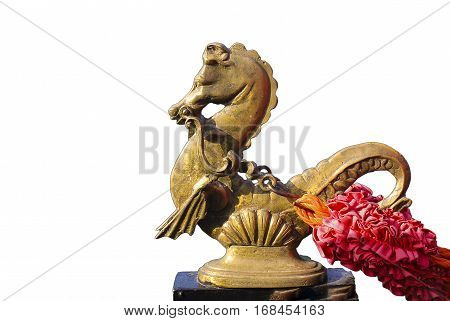 isolated bronze figurine of a sea horse with a red ornament