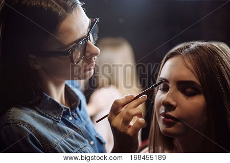 Eyebrows makeup. Attractive nice young woman sitting and closing her eyes while having her eyebrows painted