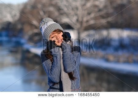 Picture of closed eyes sunny smiling beautiful cute girl enjoying a winter nature on winter snowy forest background. Portrait of beautiful girl in warm hat with balabon, sweater, scarf.