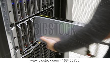 It engineer or consultant works with a blade server in data rack. Efficient and fast working in large enterprise datacenter.