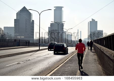 A woman is training along the way of a big city