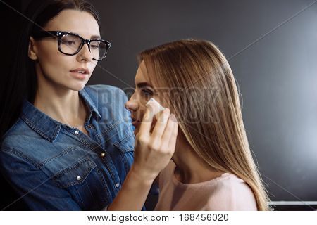 Flawless skin. Pretty brunette serious visagiste standing near her client and using a makeup sponge while making her skin look flawless