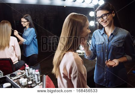 Concealing skin imperfections. Cute happy brunette makeup artist holding cosmetic powder and putting it on her clients face while smiling