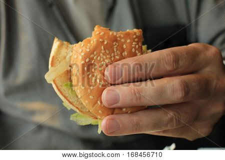 a Man holding a fresh made hamburger