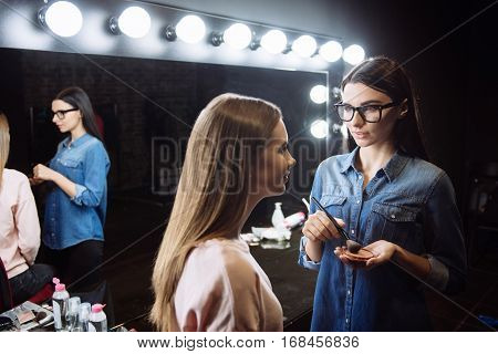 Looking natural. Attractive pleasant female visagiste holding face powder and using a makeup brush while standing in front of her client