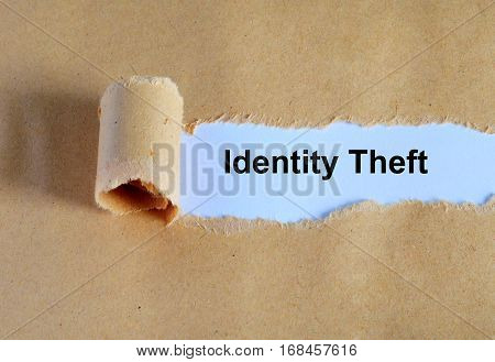 Identity Theft Word Written Under Ripped And Torn Paper.