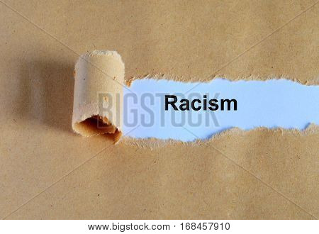 Racism Word Written Under Ripped And Torn Paper.
