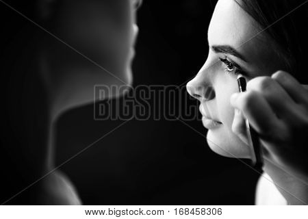 Expressive look. Professional young female visagiste using the eyeliner and drawing with it while applying makeup