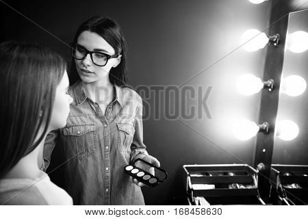 Decorative cosmetics. Beautiful pleasant female visagiste standing in front of her client and holding the eyeshadow palette while applying eyeshadow makeup