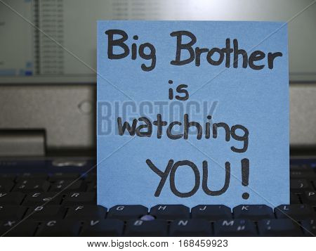 Memo note on notebook Big brother is watching you