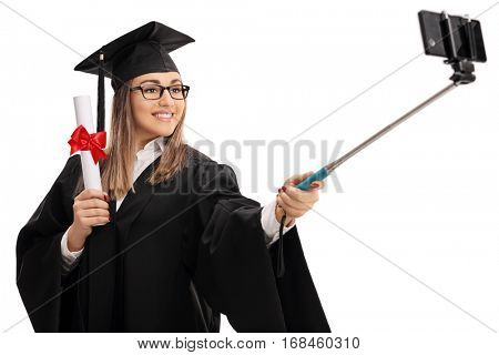 Happy female graduate student holding a diploma and taking a selfie with a stick isolated on white background