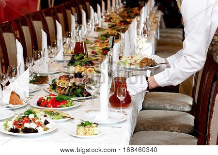 Waiter Serving Food At Luxury Table Set At Wedding Reception, Catering In Restaurant