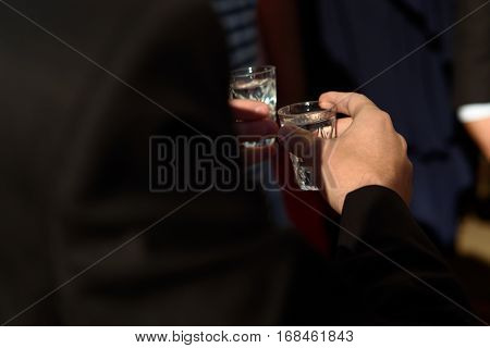 Hands Of People Clinking And Toasting With Glasses Of Vodka At Wedding Reception