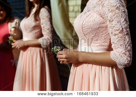 Stylish Bridesmaids In Pink Lace Dress Holding Simple Boutonniere At Wedding Ceremony