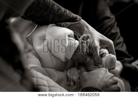 Christening Of Little Baby In Church, Close-up Feet And Priest Hand, Black And White Photo