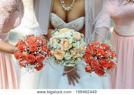 Happy Bride And Bridesmaids Showing Their Luxury Bouquets At Gorgeous Wedding Reception