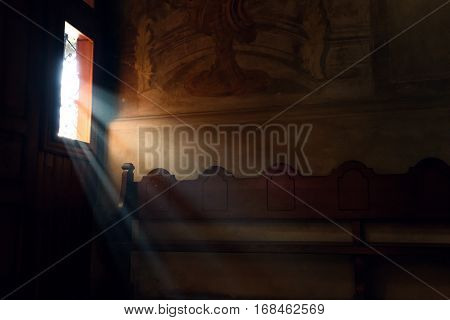 light falling through window in old church on wooden bench peaceful moment