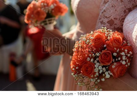 Stylish Bridesmaids In Pink Lace Dress Holding Amazing Bouquets Of Roses At Wedding Ceremony