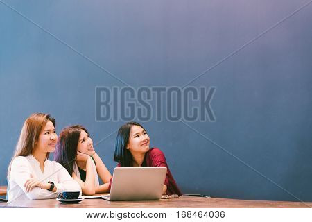 Three beautiful Asian girls looking upward to copy space while working at cafe modern lifestyle with gadget technology or working woman on casual business concept