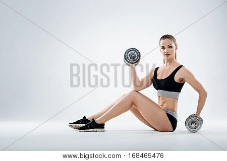Strong will. Athletic young delighted girl posing with dumbbells while standing on a grey background and training.