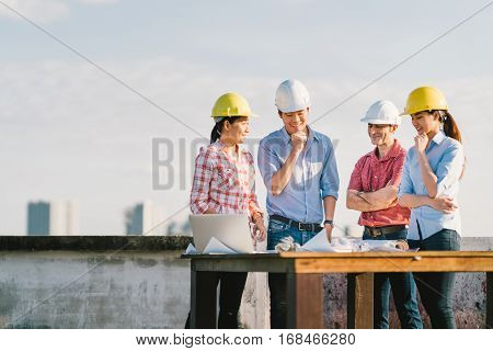 Multiethnic diverse group of engineers or business partners at construction site working together on building's blueprint architect industry or teamwork concept