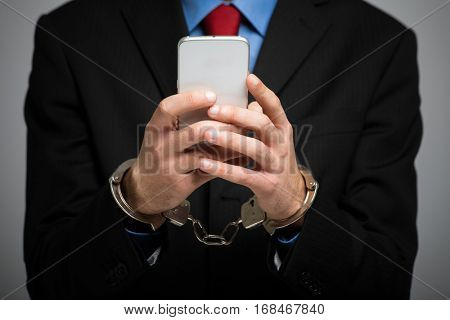 Businessman holding his phone with handcuffs, technology slave concept
