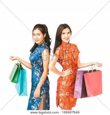 Two Asian women in Chinese qipao traditional dress holding shopping bags Chinese new year or shopaholic girls concept isolated on white background