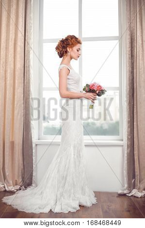Wedding. Beautiful bride indoors with bouquet of flowers against big window in full lenght