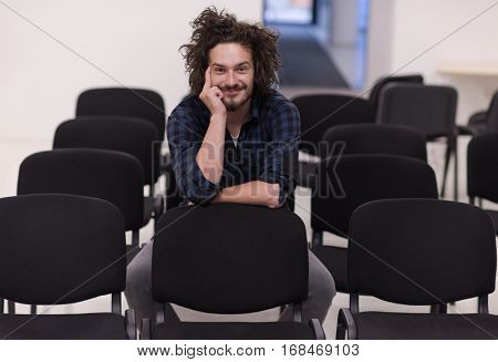 A student sits alone in a empty seats in a classroom