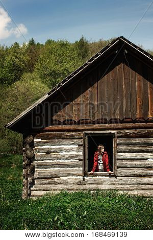 Stylish Woman Hipster Traveler Looking Through Old Window In Wooden Cabin In Sunny Mountains, Space