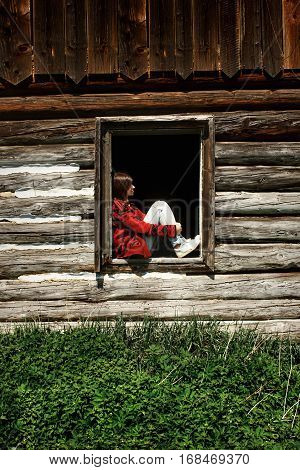 Stylish Woman Hipster Traveler Sitting And Relaxing On Old Window In Wooden Cabin In Sunny Mountains