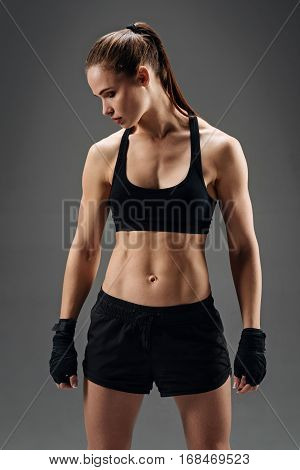 Protected and successful. Slim young active girl posing with elastic sport bandage while wearing sportswear on a grey background after having workout.