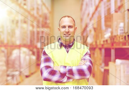 wholesale, logistic, people and export concept - happy man in reflective safety vest at warehouse