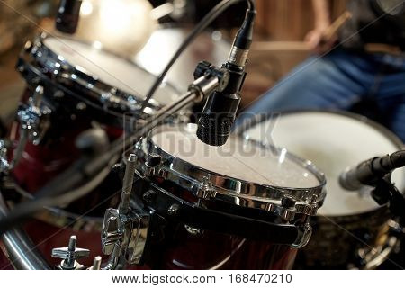 musical instruments and entertainment concept - drums and microphone at music studio