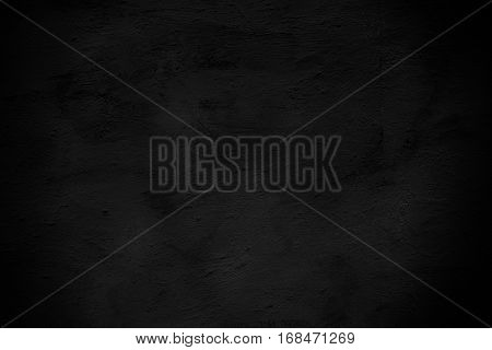dark surface of the cement plaster wall. Black background. Grunge wallpaper